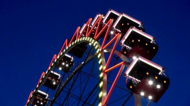 hellen riesenrad in einem freizeitpark in der nacht leuchtet mit bunten lichtern und beleuchtung verwandelt sich - volksfest stock-videos und b-roll-filmmaterial