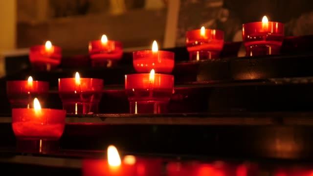 vidéos et rushes de les langues vives de feu des bougies votives rouges de prière catholique dans le rack - vaisselle picto
