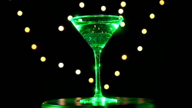 Bright green cocktail in glass, spinning on dark background with blurred light. video