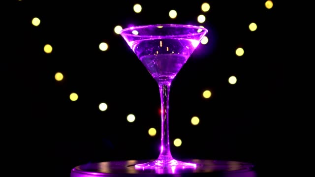 Bright magenta cocktail in glass, spinning on dark background with blurred light. video