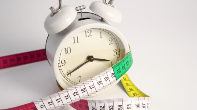 Bright measuring tape falls on a white classic alarm clock.