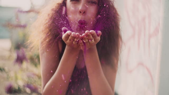 Bright pink glitter being blown by a teenage girl video
