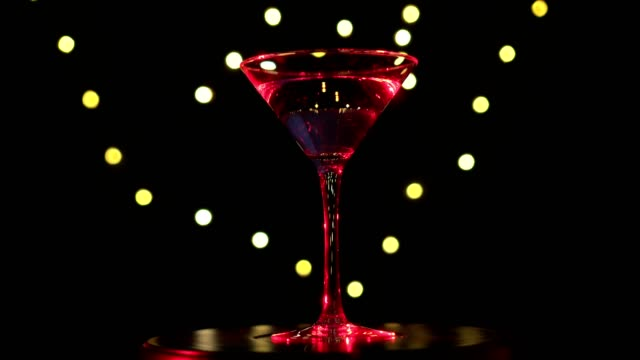 Bright red cocktail in glass, spinning on dark background with blurred light. video
