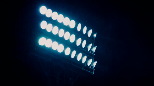 A bright spotlight on a sports stadium shines in the dark sky Searchlight tower on a dark sky background. Mast with spotlights illuminate on stadium and night sky background. Multiple sport light. A mast with a searchlight in a sports stadium. floodlit stock videos & royalty-free footage