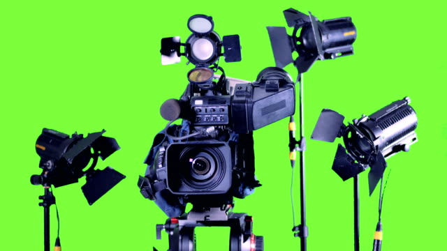 Bright spotlights stand near professional video camera on a green screen. video