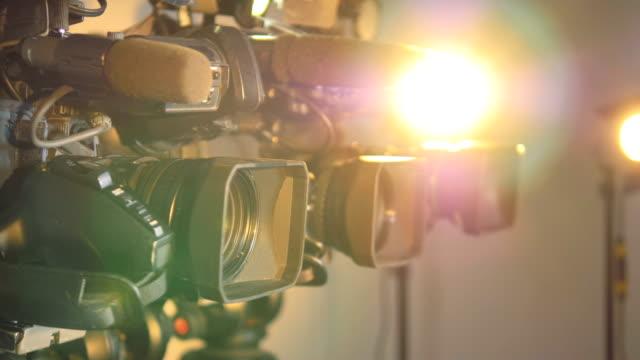 ljusa strålkastare stå nära flera videokameror. - filma bildbanksvideor och videomaterial från bakom kulisserna