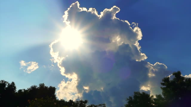 Bright sun beams rays showing behind big white cloud on blue sky background video