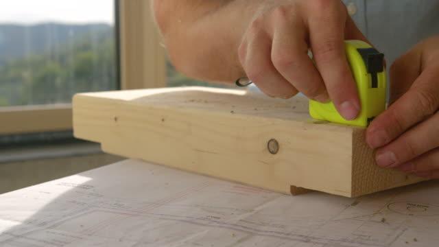 närbild: starkt solljus lyser på en entreprenör som mäter en träbit. - solar panel bildbanksvideor och videomaterial från bakom kulisserna