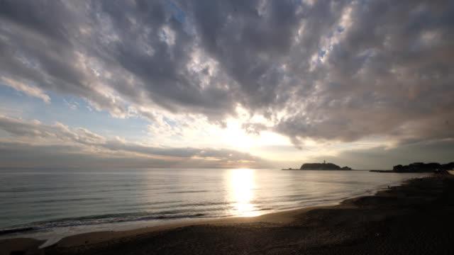 vídeos de stock e filmes b-roll de bright sunset of enoshima island in kanagawa japan. sea waves against coastline. - linha do horizonte sobre água