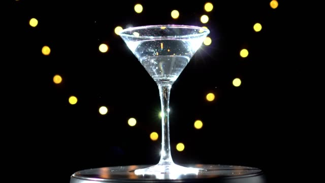 Bright white cocktail in glass, spinning on dark background with blurred light. video