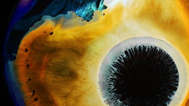 ljusgul och blå reaktion med flytande bläck / big bang av supernova - akrylmålning bildbanksvideor och videomaterial från bakom kulisserna