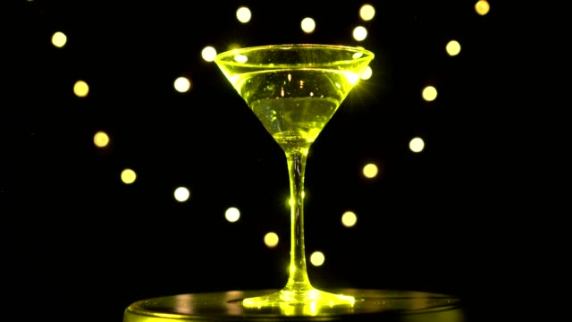 Bright yellow cocktail in glass, spinning on dark background with blurred light. video