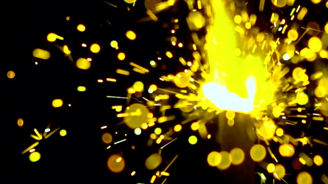 Bright yellow sparkler against dark background. Super slow motion shallow focus video, 500 fps video