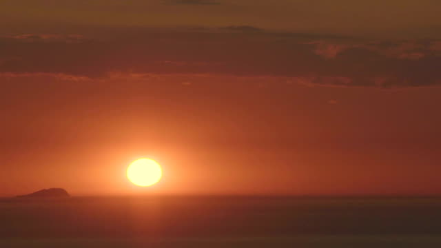 Bright yellow sun going down on horizon, beautiful sunset, endless seascape Bright yellow sun going down on horizon, beautiful sunset, endless seascape horizon over land stock videos & royalty-free footage