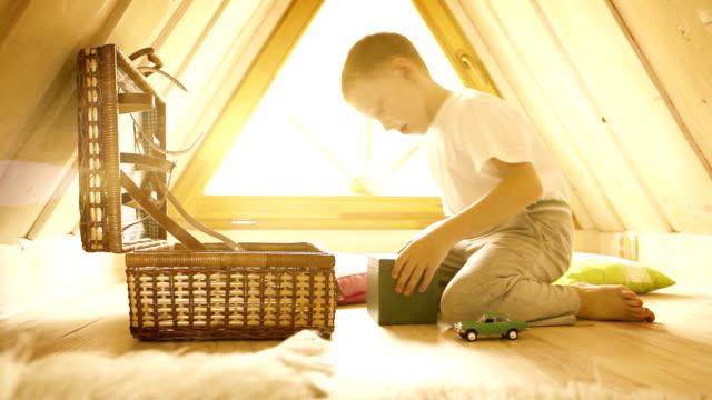 hell gelb-sepia aufnahmen von eine junge spielt in seinem attic zimmer - dachboden stock-videos und b-roll-filmmaterial