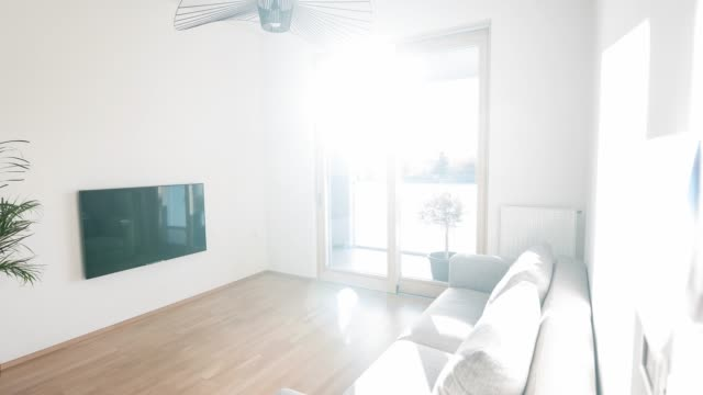 Brightly lit living room in an open floor plan apartment with minimalist furnishing Brightly lit modern living room in an open floor plan apartment with minimalist furnishing, panning left living room stock videos & royalty-free footage