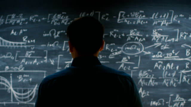 Brilliant Young Academic  Approaches  Blackboard with Complex Mathematical Formula Written on it, Starts Thinking about Solution.