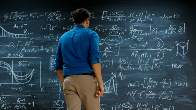 Brilliant Young Mathematician Approaches Big Blackboard and Thinks about Solving Long and Complex Equation/ Formula. Brilliant Young Mathematician Approaches Big Blackboard and Thinks about Solving Long and Complex Equation/ Formula. Shot on RED EPIC-W 8K Helium Cinema Camera. complexity stock videos & royalty-free footage