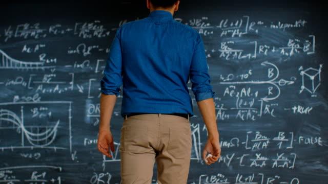 Brilhante matemático jovem se aproxima Blackboard e acabamentos resolver equação de longa e complexa. - vídeo