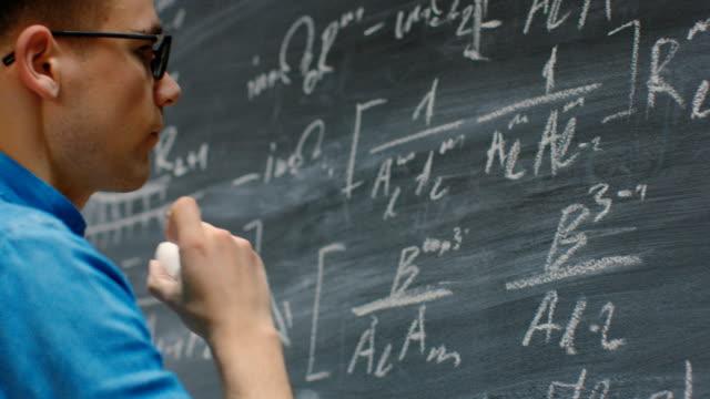 vídeos de stock e filmes b-roll de brilliant young mathematician writes complex math equation/ formula on the blackboard. - dedicação