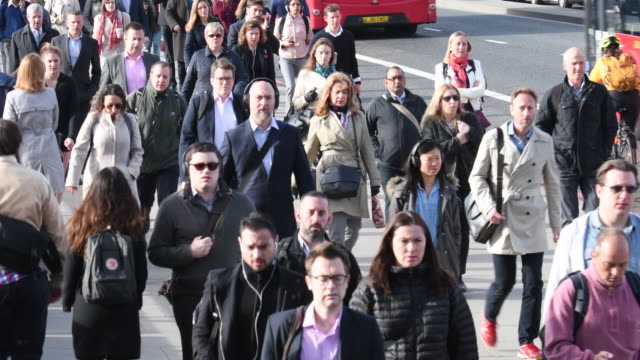 British business people on morning commute walking to work across London Bridge video