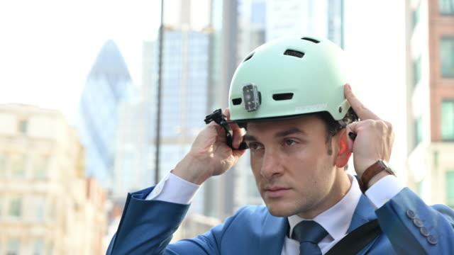 British businessman putting on bike helmet for commute