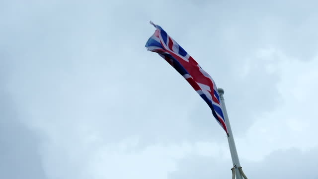 British flag blowing against an overcast sky, filmed in 5 X slow-motion. video