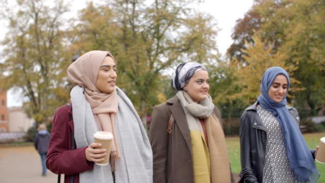 British Muslim Female Friends Walking Through City Park video