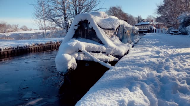 british narrow boat on canal waterway in deep snow during cold winter - england stock videos & royalty-free footage