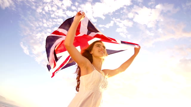 British woman holding Union Jack flag waving in slow motion video