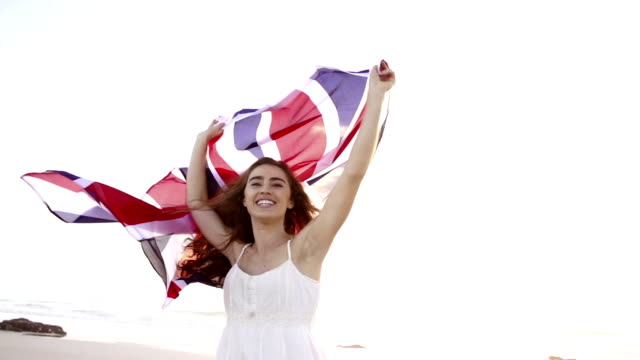 British Woman spinning with Union Jack on beach video