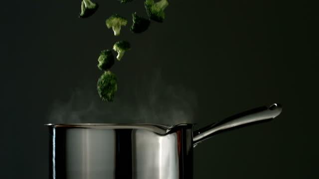 broccoli cade in acqua bollente, rallentatore - broccolo video stock e b–roll