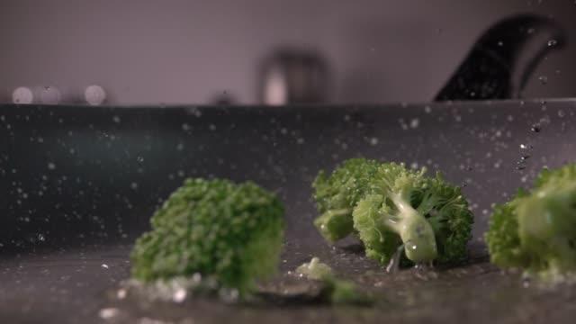 vídeos de stock e filmes b-roll de broccoli pieces being dropped into a frying pan in slow motion, 480 fps - brócolo