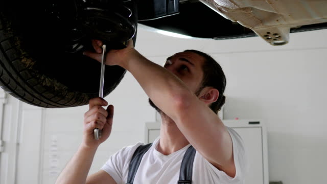 broken automobile in auto dealership, mechanic working at workshop, fix Car parts, Car service, young specialist repairs cars video