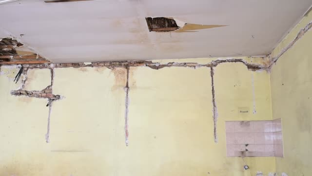 broken damaged and collapsed ceiling and roof of old dark house abandoned after aftermath disaster and heavy rain water leak selective focus - foro video stock e b–roll
