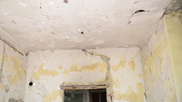 Broken damaged and collapsed ceiling and roof of old house abandoned after aftermath disaster and heavy rain water leak selective focus