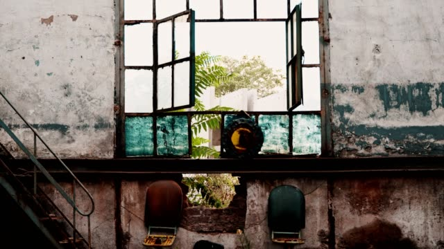 Broken glass window of an old abandoned building opens and closes with the wind