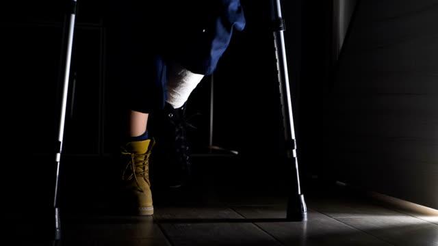Broken leg, disability, handicap - Injured man wlaking with crutches - indoor Broken leg, disability, handicap - Injured man wlaking with crutches - indoor crutch stock videos & royalty-free footage