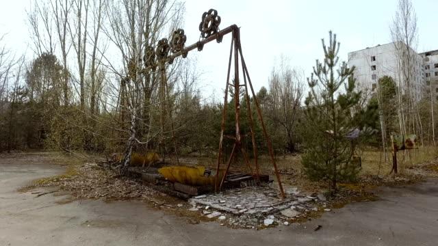 Broken old swing in the city of Pripyat. Ukraine, Pripyat, 6 april 2017 Broken old swing in the city of Pripyat. Ukraine, Pripyat, 6 april 2017 time zone stock videos & royalty-free footage