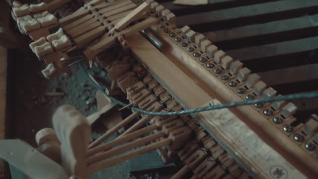 Broken parts of a piano lie in a ruined building amidst garbage