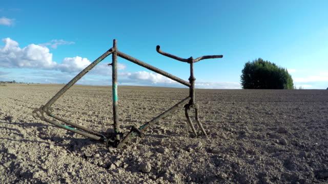broken rusty bicycle frame on farm field. Timelapse video