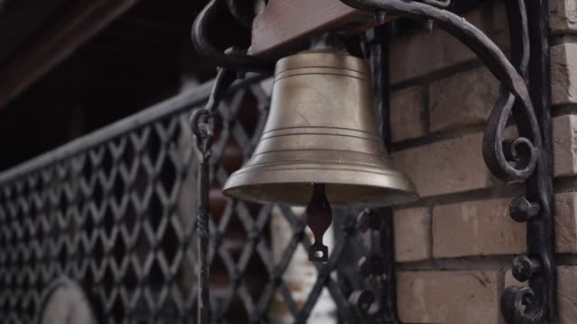 A bronze bell hanging on the wall near the gate