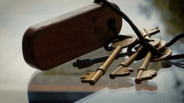 bronze keys tied with string to wooden key fob - key ring stock videos & royalty-free footage