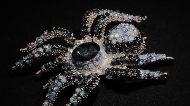Brooch in the form of a spider on a black rotating stand. Premium Jewelery. Macro