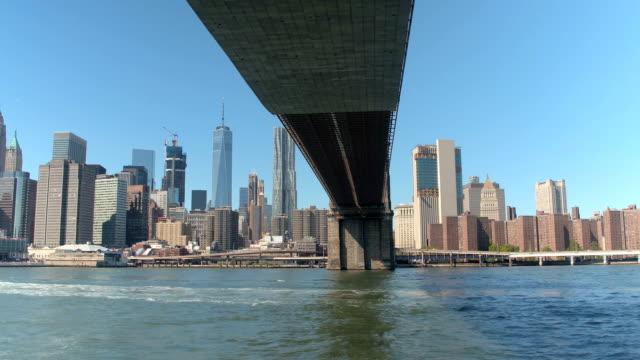 närbild: brooklyn bridge och downtown manhattan skyline från east river - flod vatten brygga bildbanksvideor och videomaterial från bakom kulisserna
