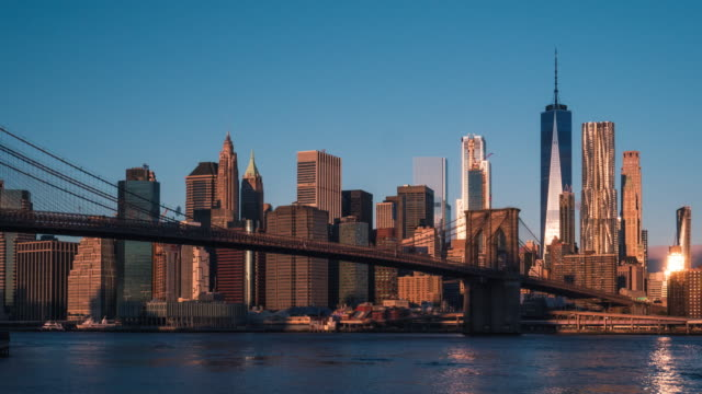 Brooklyn Bridge and NYC Sunrise Time Lapse Time-lapse of the Brooklyn Bridge and New York city skyline during sunrise on a beautiful autumn day. Shot in 4K resolution. new york architecture stock videos & royalty-free footage