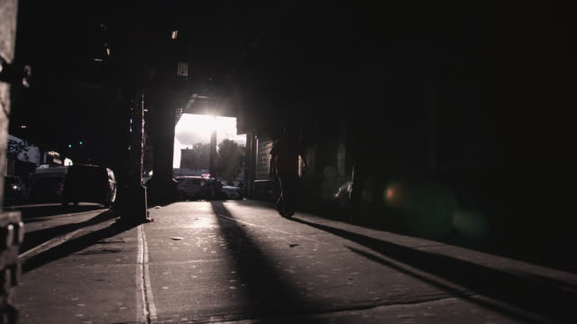 Brooklyn underpass at sunset. Figures walking beneath a Brooklyn underpass cast shadows across the sidewalk. back lit stock videos & royalty-free footage