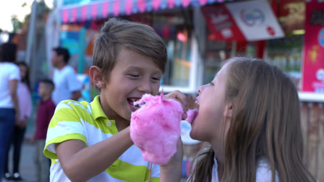 Brother and sister at a fun fair sharing cotton candy and pop corn having a great time video