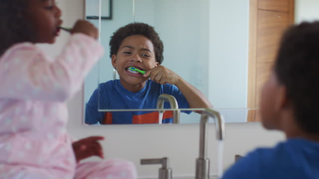 brother and sister brushing teeth reflected in bathroom mirror at home - denti video stock e b–roll