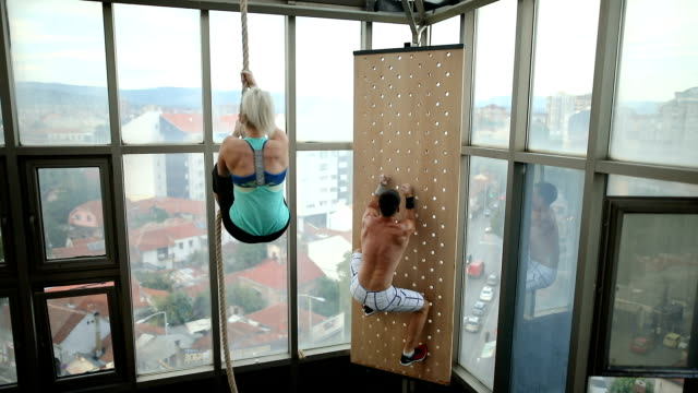 brother and sister climbing thick rope during fitness exercises - inerpicarsi video stock e b–roll